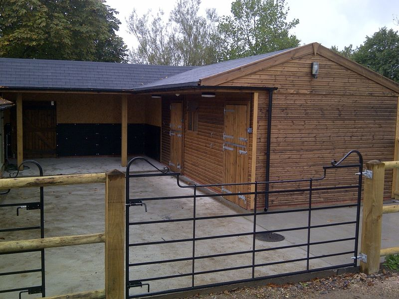 Stables with shoeing/washdown area with shingle roof image #1